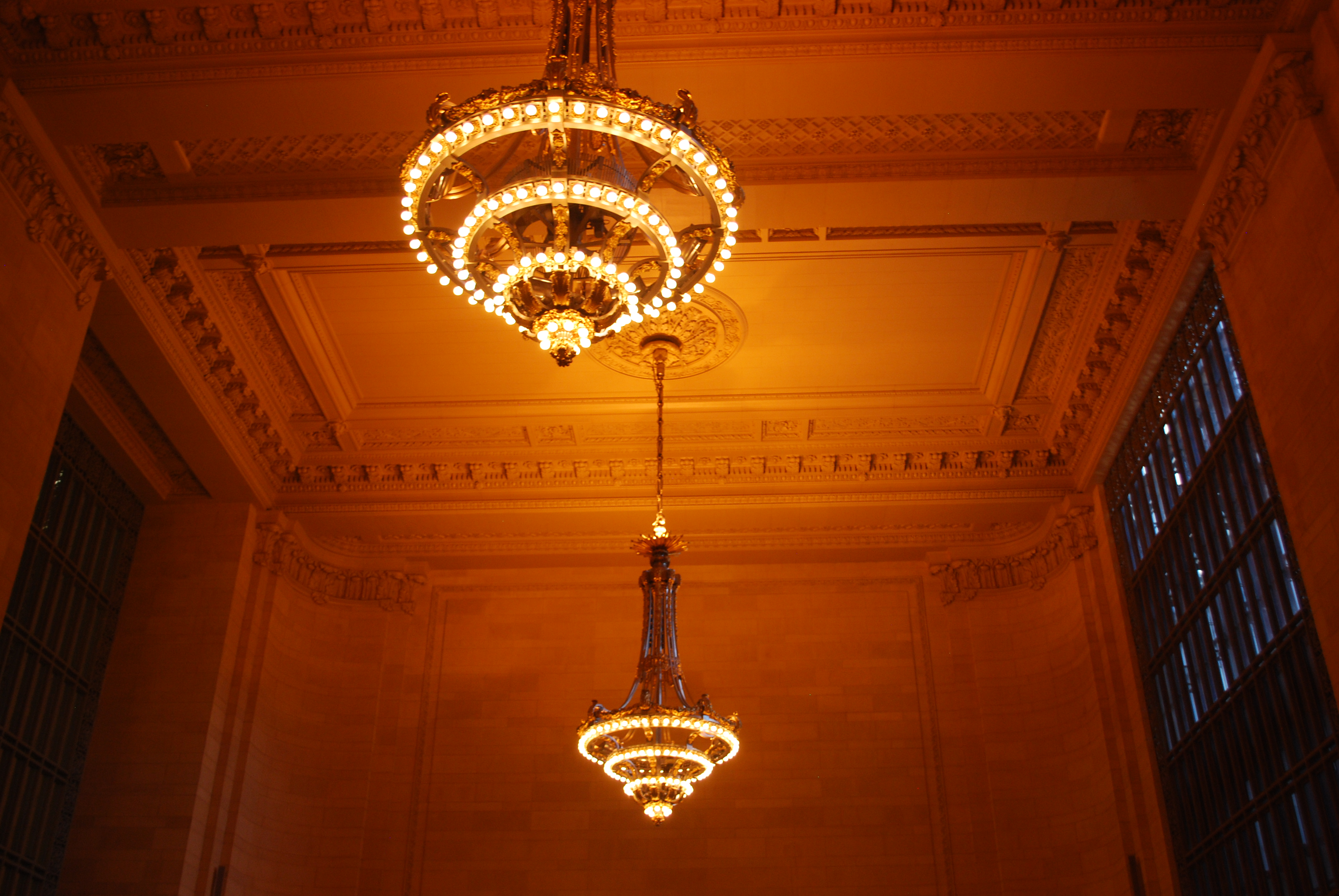 Two chandeliers glowing in the lobby of Grand Central Station.